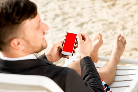 sunbed: Businessman holding cellphone with empty screen sitting on the sunbed dressed in suit and shorts on the beach Stock Photo