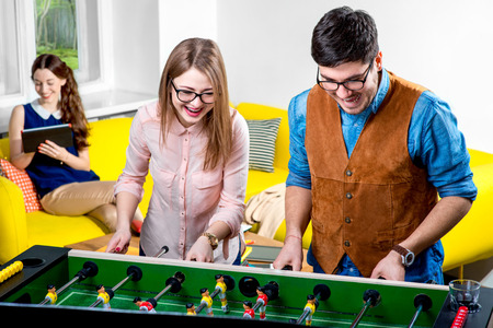 Young friends or students having fun together playing table football photo