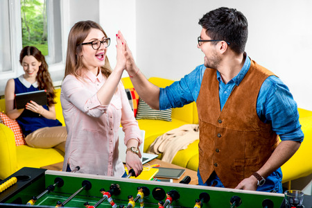 joyfull: Young friends or students having fun together playing table football