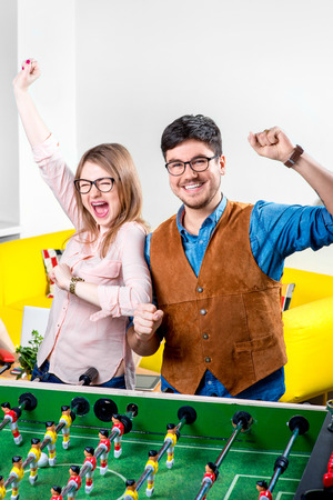 Young couple having fun together playing table football photo