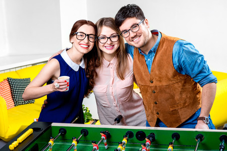 Young friends or students having fun together embracing after the table football game photo
