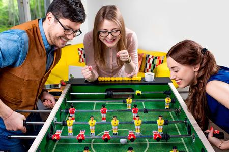 Jeunes amis ou des étudiants ayant du plaisir ensemble jouant baby-foot