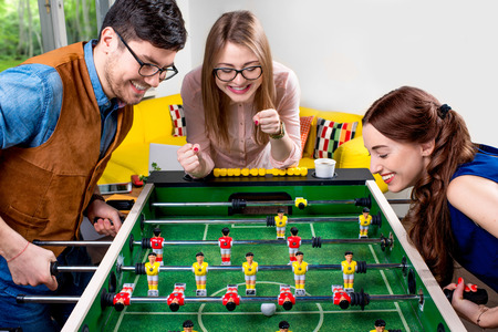 Young friends or students having fun together playing table football