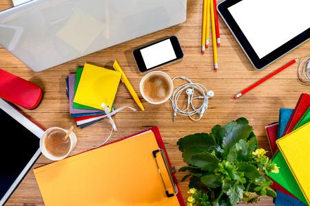 Digitální Gadgets s různými barevnými věci a kávy na dřevěném stole. Pohled shora