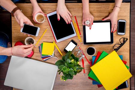 muchas personas: Trabajar o estudiar con aparatos digitales y diferentes cosas colorido y el caf� en la mesa de madera. Vista superior Foto de archivo