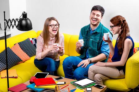 riendose: Amigos hablando y riendo con tazas de caf� en el sof� amarillo Foto de archivo