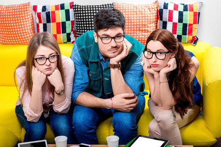 wearied: Three nerds in eyeglasses sitting on the couch and looking at camera Stock Photo