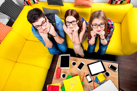 wearied: Three nerds in eyeglasses sitting on the couch and looking at camera with different gadgets on the background