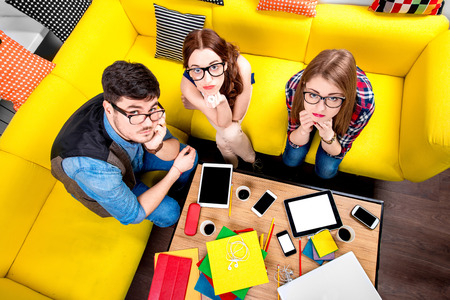 Three nerds in eyeglasses sitting on the couch and looking at camera with different gadgets on the background