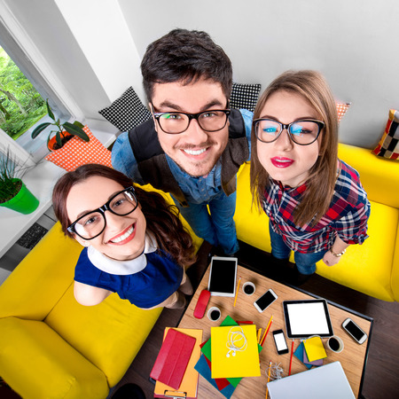 man with glasses: Three funny nerds looking together at camera standing in the room with couch and different digital stuff on background