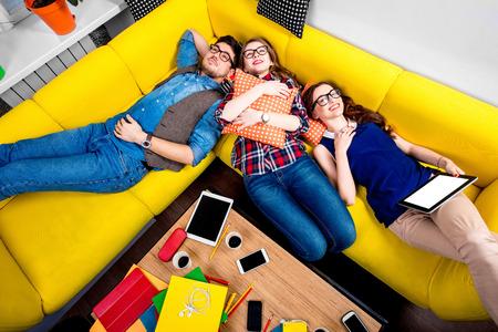 jovenes estudiantes: Dormir y cansados ??j�venes estudiantes sintieron sue�o despu�s del trabajo en el sill�n amarillo
