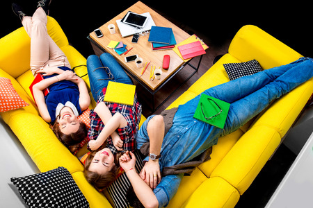 wearied: Sleeping and tired young students felt sleep after work on the yellow couch