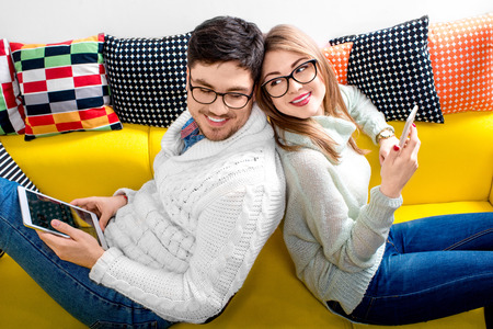 cosiness: Young couple in sweater and eueglasses with tablet sitting on the couch at home
