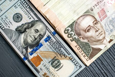 Ukrainian and American money banknots on wooden background photo