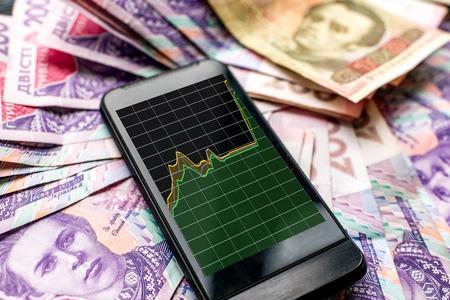 devaluation: Phone with devaluation schedule on a pile of ukrainian money