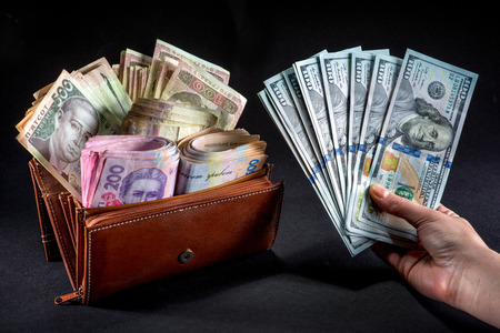 hryvna: Pile of Ukrainian money in the wallet and american dollars in the hand on black background