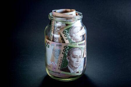 hryvna: Ukrainian five hundred banknots in the jar on black background