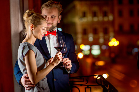 Loving couple with wine glasses embracing on the balcony on the night city background