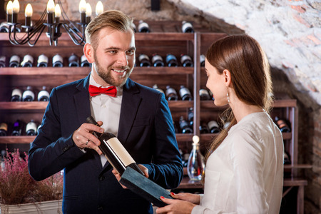 sommelier: Sommelier showing wine bootle to woman in the wine cellar