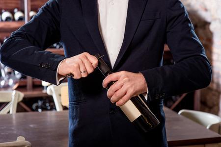 ソムリエがワインのセラーでワインのボトルを開く
