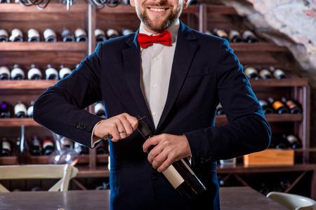 sommelier: Sommelier opening wine bottle in the wine cellar