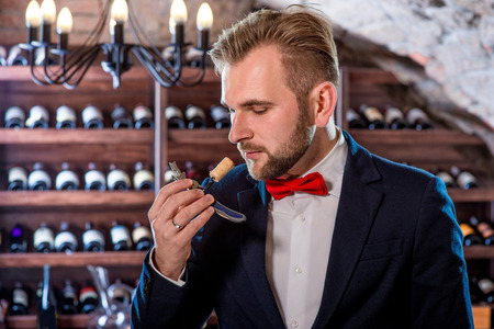 sommelier: Sommelier smelling corck in the wine cellar