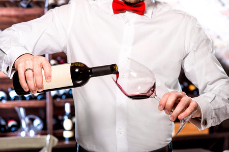 wine tasting: Sommelier pouring wine to the glass in the wine cellar Stock Photo