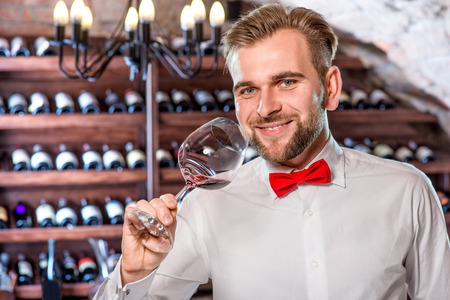 sommelier: Sommelier checking wine in the glass in the wine cellar