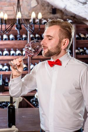 sommelier: Sommelier tasting wine in the wine cellar