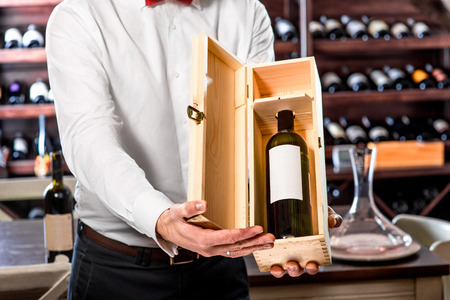 Sommelier showing wooden wine box with expensive wine in the wine cellar