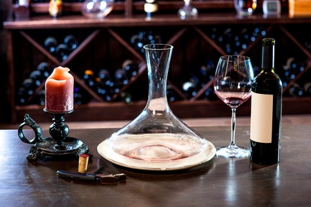 decanter: Decanter with wine and candle in the wine cellar
