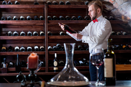 Sommelier looking for good wine on the storage in the wine cellar photo