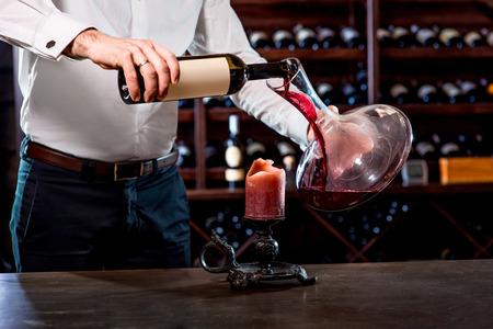 ソムリエのワイン貯蔵室のデカンターにワインを注ぐ