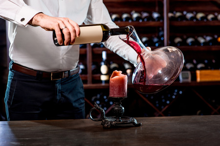 Sommelier pouring wine to the decanter in the wine cellar Archivio Fotografico