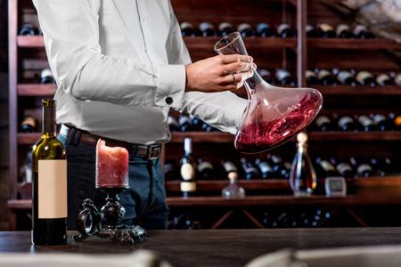 소믈리에 와인 저장고의 데 칸타에 와인을 쏟아 부음