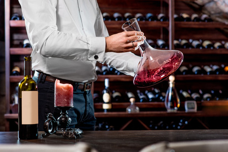 pouring wine: Sommelier pouring wine to the decanter in the wine cellar Stock Photo