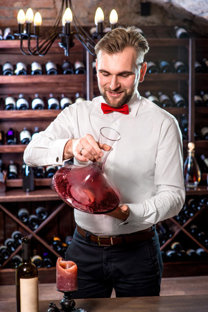 Sommelier mixing wine in the decanter in the wine cellar photo