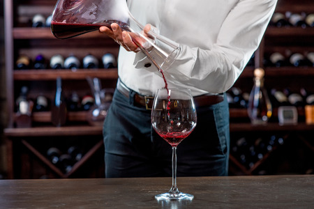 pouring wine: Sommelier pouring wine to the glass in the wine cellar Stock Photo