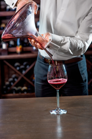 Sommelier pouring wine to the glass in the wine cellar Stock Photo