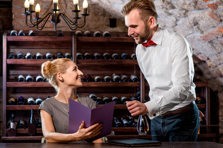 relishing: Sommelier helping young woman to choose wine in the cellar. Wine degustation