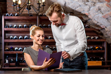 degustation: Sommelier helping young woman to choose wine in the cellar. Wine degustation