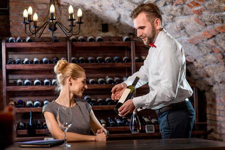 ソムリエのセラーでワインを選択する若い女性を助けます。ワインのデギュスタシオン