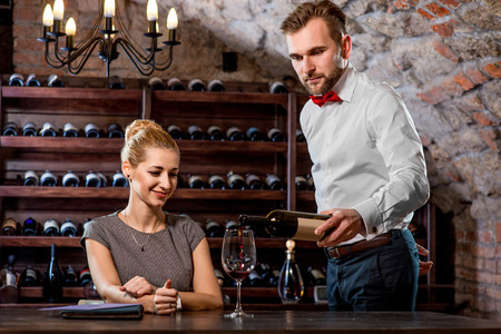 degustation: Sommelier pouring wine to the glass with woman in the cellar. Wine degustation Stock Photo