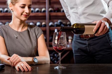 sommelier: Sommelier pouring wine to the glass with woman in the cellar. Wine degustation Stock Photo