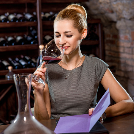 Young woman tasting wine in the cellar. Wine degustation Imagens