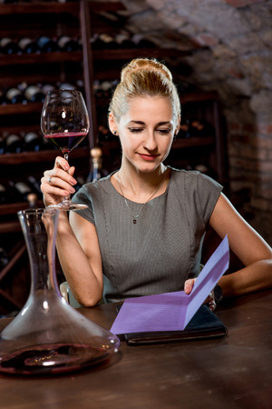 offish: Young woman tasting wine in the cellar. Wine degustation Stock Photo