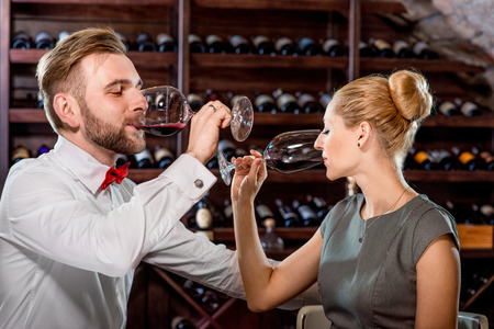 twee: Romantic well-dressed couple drinking wine at the cellar