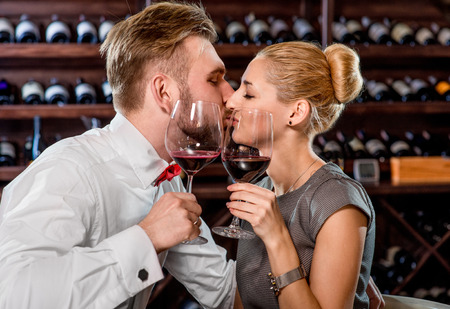winetasting: Young well-dressed couple kissing and having romantic wine tasting at the cellar