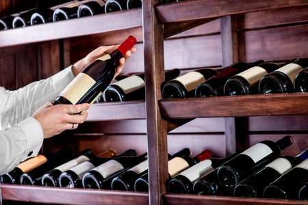Sommelier choosing a bottle of wine at the wine cellar Stock Photo