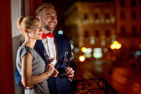 romantic evening with wine: Loving couple with wine glasses embracing on the balcony on the night city background
